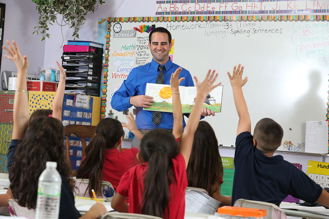 Male teacher reading in front of young students raising hands